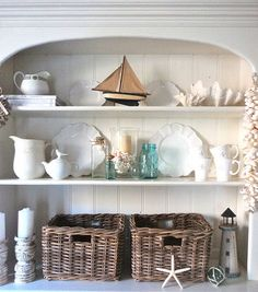 Beach style hutch decorating idea: Mini boat, large shells, star fish, mini light tower, glass ball in rope, shabby chic candle holders, woven bins, cream plates on display, blue glass jars, strung shells.
