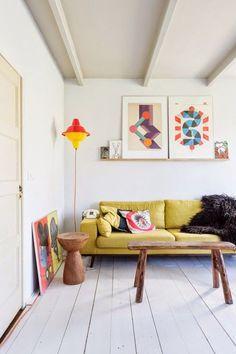 sofá amarelo na decoração da sala de estar. mesa de madeira e quadros coloridos apoiados em prateleira acima do sofá