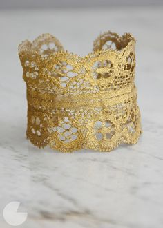 Tutorial for this golden lace cuff. She uses Elmer's glue. I wonder if you can Mod Podge it...? Wait. I Podge everything, of course I can Podge lace. Think I'm gonna get red though. Lace, not Podge.