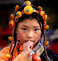 Little girl in ceremonial costume in Yushu. The yellow beads in her headdress are synthetic. Traditional dress for girls and women includes braided hair,  for grown women often 108 braids are made, as 108 is a holy number in Tibetan buddhism