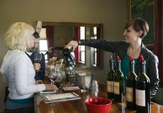 Julie Brown, from right, pours wine tastings for Darrell McKnight and Kristine Pedigo during the annual spring barrel tasting event at Reflection Vineyard in Zillah, Wash. on April 24, 2015. (KAITLYN BERNAUER/Yakima Herald-Republic)