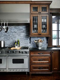 Contemporary tile makes the dark, traditional cabinets in this kitchen stand out! More of our favorite tile ideas here: http://www.bhg.com/kitchen/backsplash/backsplash-pairings/?socsrc=bhgpin062414traditionaltwist&page=4