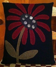 This is a great primitive penny rug pillow which is designed and handmade by me. The pillow measures 11 by 13 inches. The base is black wool. The design features a cranberry red flower with charcoal