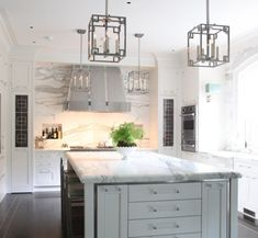 glass drawer pulls?!? kitchen with marble cabinets, an island, detailed upper cabinetry, a stainless hood and lantern pendant lights