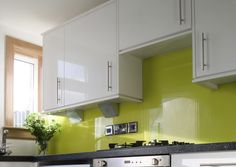 This kitchen looks like it is a very fun and exciting room. I think that the glass splashback has a lot to do with it. The green color seems to lighten up the room and give it energy.