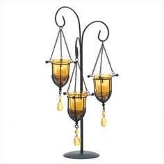 "Sunset colors dazzle with the warmth of captured light, turning this graceful stand into a blaze of beauty! Artfully fashioned from matte black metal with golden-amber glass candle cups.Weight 1.6 lbs. UPC# 817216010453. 10"" diameter x 20"" high. Iron, glass and acrylic accents. Votive candles not included."