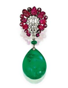 Carved Ruby and Diamond Clip-Brooch, by Cartier, London, with an Emerald Pendant. Photo Sotheby's    The Colombian emerald drop weighing over 100 carats.