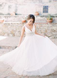V-neck dress by Bella Wedding Brida: http://www.stylemepretty.com/california-weddings/san-juan-capistrano/2016/08/23/al-fresco-serra-plaza-wedding/ Photography: Kristina Adams - http://www.kristinaadamsphotography.com/