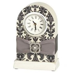 "Desk clock with a damask motif and ribbon.    Product: ClockConstruction Material: Wood and ribbonColor: Ivory and blackAccommodates: Batteries - not includedDimensions: 6"" H x 4"" W x 2"" D"