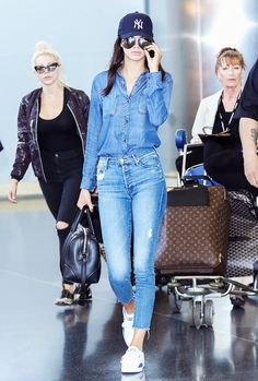 Kendall Jenner wears a denim shirt, cropped jeans, Puma sneakers, a Givenchy duffle bag, and a Yankee hat