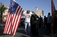 """Two demonstrators stand in front of the Islamic Community Center to oppose the """"Freedom of Speech Rally Round II"""" across the street in Phoenix, Arizona May 29, 2015. Arizona police stepped up security near a mosque on Friday ahead of a planned anti-Islam demonstration featuring displays of cartoons of the Prophet Mohammad, weeks after a similar contest in Texas came under attack from two gunmen.  REUTERS/Nancy Wiechec      TPX IMAGES OF THE DAY"""