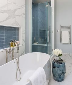 The blue color is repeated around the room with the tile niche, small drum table and bathroom vanity cabinet color. A heated towel bar, from Mr. Steam, is a nice luxury addition to any bathroom.  Bathroom Remodel - Carla Aston, Designer | Photographer, Colleen Scott White Bathroom, Bathroom Interior, Heated Towel Bar, Penny Tile Floors, Marble Look Tile, Best Bathroom Designs, Drum Table, Guest Bathrooms, Home Decor Paintings