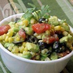 Frisse schijfjes avocado gemengd met zoete maïs, olijven, rode paprika en ui. Een kleurrijke dip met een Mexicaans tintje, serveren met tortillachips, in een wrap of als bijgerecht tijdens een barbecue.