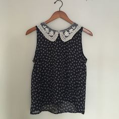 Collared Navy Top A delicate navy tank top with a beautiful lace collar and pearl clasp in the back. The design on the shirt depicts little white bows. Never been worn. Tops Tank Tops