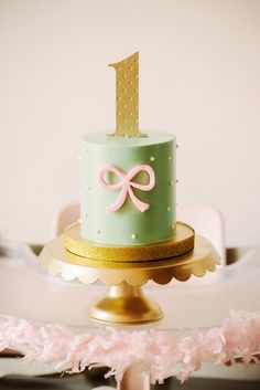 "Bow Smash Cake: ""Blake needed a smash cake as well,"" Melody of Sweet and Saucy Shop says of her daughter's bow-filled first birthday party. ""We did a simple mint buttercream cake with a cute little bow, polka dots, and an adorable topper from Little Cat Design.""  Source: Sweet and Saucy Shop"