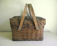 For your modern farmhouse is this charming woven splint picnic basket with a lid. The basket has a sturdy wood frame bottom, a wire hinge and latch for the woven lid and a pair of long swing handles. Lovely vintage basket for storage and display. The hinge and latch work well, but the lid is a bit out of shape compared to the bottom, so the latch fits tight. • bottom measures 15 x 9 by 7 1/4 high or 10 high including closed lid • in wonderful vintage condition, sturdy with wear but no b...