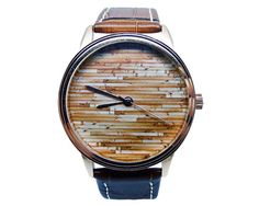 This listing is for one mens watch featuring a wood design on the face. The watch has a brown genuine leather strap, a gold coloured case and gold hands.