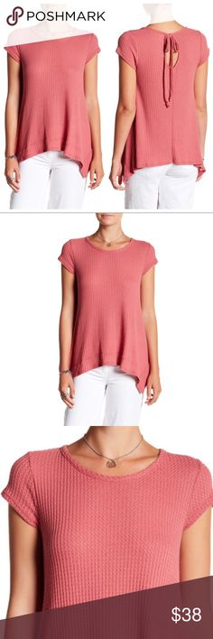 "🔴 Waffle Knit Tie Back Tee Details Dainty cap sleeves frame a thermal tee with an edgy asymmetrical hem that exudes effortless style. - Crew neck - Short sleeves - Back keyhole with self-tie nape closure - Waffle-knit construction - Banded sharkbite hem - Approx. 24.5"" shortest length, 29"" longest length (size S)  Fiber Content 62% polyester, 33% rayon, 5% spandex Care: Hand wash cold Fit: this style fits true to size.  Model's stats for sizing: - Height: 5'8"" - Bust: 34"" - Waist: 24""…"