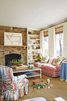 Design by Bailey McCarthy: Country Living April 2015 Farmhouse living room // family room // pink gingham // pink buffalo check // skirted table // chintz // country family room // charm // longhorn art