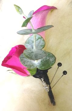 A groom's boutonniere of hot pink calla and rose with spiral eucalyptus and accented with a spark plug charm and black ribbon wrap from Seasonal Celebrations, http://www.seasonalcelebrations.com