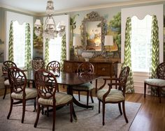 Mural-like wallpaper and patterned curtains ensure this traditional dining room doesn't feel tired or stuffy. Spider back dining chairs are enlivened with green upholstered seats, and a stunning chandelier crowns the space.