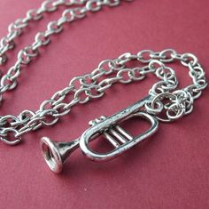 This cute silver plated metal  trumpet charm with chain necklace is perfect for the elementary band or orchestra student.  High school band or orchestra students may also enjoy wearing this, however,