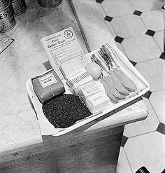 Ration book and an adult's weekly rations of basic foodstuffs, 1942. Food rationing began on 8th January 1940 and continued until 30th June 1954. Clothes, sweets and soap were also rationed, and almost all other consumer goods were in short supply.