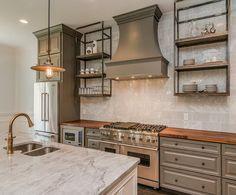 Vintage kitchen features mini vintage barn pendants illuminating a white center island with turned ...
