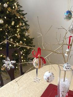 A real North Carolina branch was sacrificed for this display. A little gold spray paint and stuffed in a crystal glass with beads.  A creative way to display special keepsake ornaments