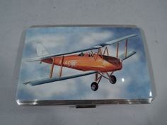 Only one in stock of this item shown. Postwar Aviation Nostalgia – English Sterling Silver and Enamel Case Contact: 646-863-5416 Elizabeth II sterling silver and enamel cigarette case. Made by Willian Neale & Sons, Ltd in Birmingham in 1956. Rectangular and hinged with chamfered corners. On cover in enamel is an early 2-seater airplane piloted through blue sky and fluffy white clouds. A serene depiction of flight only a few years after World War II. The scene is between reeded silver…