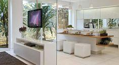 Cozinha gourmet com portas pivotantes de vidro no lugar de janelas. Bancada com cooktop e solução integrada ao espaço de TV.