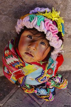Quechua girl wearing a pollera, jobona, and a hat. The image shows the…