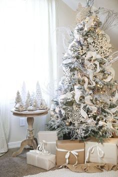 white Christmas tree with lots of ornaments oversized snowflakes, pinecones and a chic ribbon garland