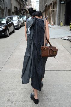 wearing Comme des Garcons __ it looks like it has alternative shape modes... that you can take those extra pieces hanging off the back and slip them over the head & arms. In fact, it looks like two extra dresses attached on the back.
