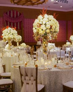 At this Christmas-inspired nuptials, half the tables were adorned with tall glass vases that were filled with metallic ornaments and topped with arrangements of white roses, hydrangea, and peonies, with gold-sprayed foliage and red berries all from Gillespie's Flowers. Low versions of the arrangements filled the other tables.