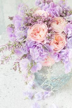 Violet flowers with peach pink roses in glass vase, purple wedding table decor inspiration.