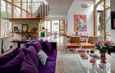 Escada vazada com estrutura de rampas de concreto e degraus de madeira. Para tornar os ambientes mais aconchegantes, o casal revestiu a maioria dos ambientes com assoalho de madeira