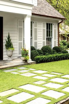 """A Birmingham Cottage: Thoughtful Landscaping - Best Before and Afters of 2016 - Southernliving. Bluestone pavers were installed in the grass to carve a distinct path leading to the revamped front door. Fitting the pavers into the grass also softened the style of the walkway. """"We didn't want the hardscape to dominate too much,"""" explains Lell. As for the greenery, Little favors boxwoods, and Lell was happy to oblige. He says, """"We wanted to play up the house's theme of 'rich in detail but also…"""