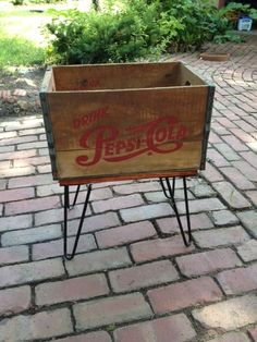Vintage hairpin legs off an old footstool put on a vintage Pepsi crate. Vintage hairpin legs off an Wooden Crate Shelves, Vintage Wooden Crates, Diy Wooden Crate, Diy Dog Crate, Old Crates, Milk Crate Seats, Coca Cola Decor, Crate Table, Crate Furniture