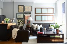 Love the wall of framed vintage maps. A small functional island or prep space is a good idea. Furniture here is too black and chunky.