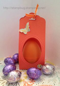 "9 1/4"" x 2"" strip, folded at 4 1/2 from each end, punched with Scallop Tag punch, embossed with the Designer Frame folder, punched with the Large Oval Punch.  Tack egg inside with glue dots."