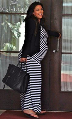 Pregnant Kim Kardashian who looks freshly sprayed tanned wearing a striped maxi visits Mr. C Restaurant in Beverly Hills eating with best friend Brittny Gastineau then stops at Ruth Chris for a second meal!