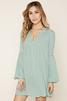 A crinkled woven mini dress featuring a split neckline, elasticized cuffs, on-seam side pockets, and ornate crochet paneling at its front, back, and long sleeves.
