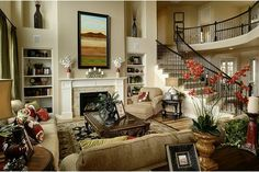 Bookshelves and a sweeping staircase flank the fireplace. New homes in the Beacon Point community by Century Communities. Aurora, Colorado