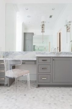 Chic bathroom features a gray built-in makeup vanity topped with gray and white marble paired with a lucite klismos chair placed atop a marble hex floor.