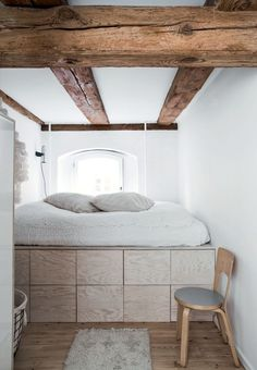 Plywood bed with storage in a bedroom with exposed beams