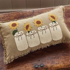 This decorative pillow features appliqued Sunflowers in mason jars in a row. Burlap like look with hand stitching around edge, back of pillow is a checked patte