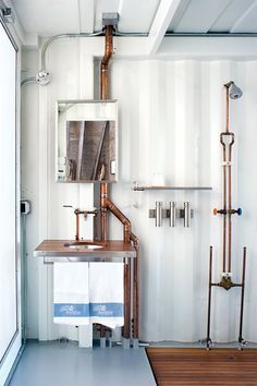 White bathroom with corrugated metal walls and copper pipes.