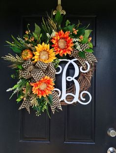 NEW ITEM! Gorgeous late Summer Early Fall Door Wreath! Perfect for greeting your guests to your home, with this one of a kind door wreath. Made up on an 18 grapevine wreath with moss, mixed flowing greenery or sunflower leaves, ferns, ficus and more! Gorgeous bright orange and yellow sparkly sunflowers with harvest wheat and white and orange accents. An adorable decorative pumpkin along with a decorative white 12 script monogram and gorgeous full black chevron burlap bow make up this very…