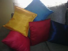 Fiber-filled throw pillows with satin multicolored covers.